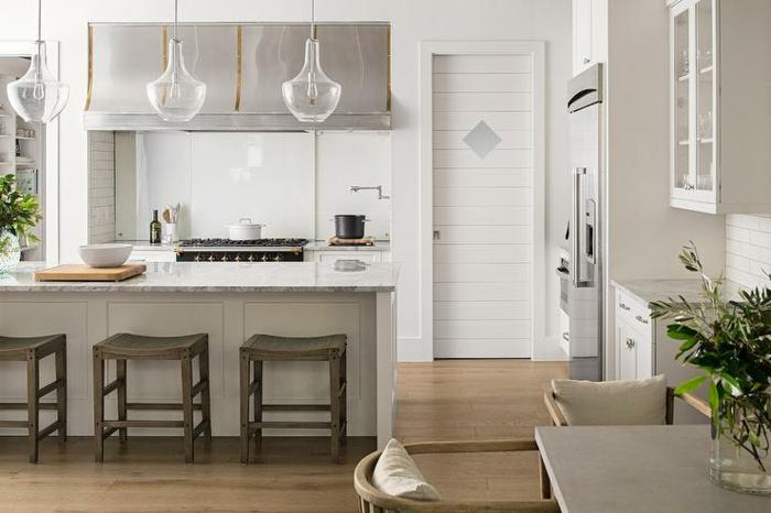 chaises en bois, lampes suspendues, armoires de cuisine suspendues, îlot de cuisine avec tabourets, petite armoire vitrée