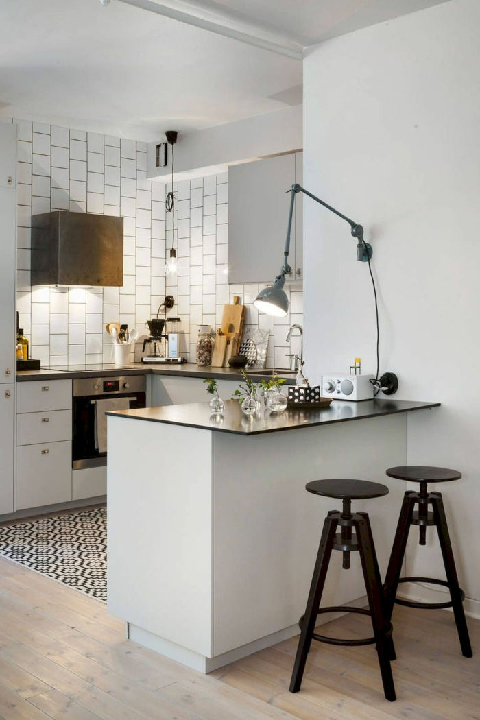 cuisine en noir et blanc, tabourets industriels, lampe bras articulé, carrelage blanc, tapis graphique