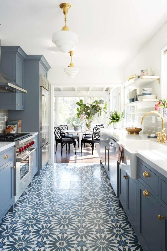 cuisine blanche et gris, chaises noires, table blanche tulipe, sol motifs carreaux de ciment, cuisinière vintage, lampes blanc et doré