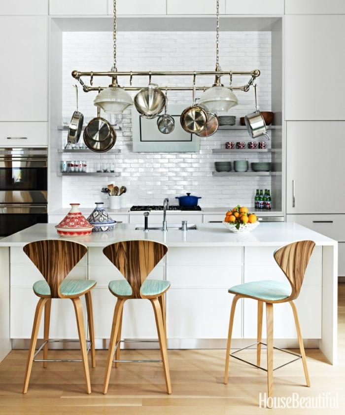 chaises en bois, ustensiles suspendus, carrelage métro blanc, étagères blanches, îlot de cuisine avec évier blanc