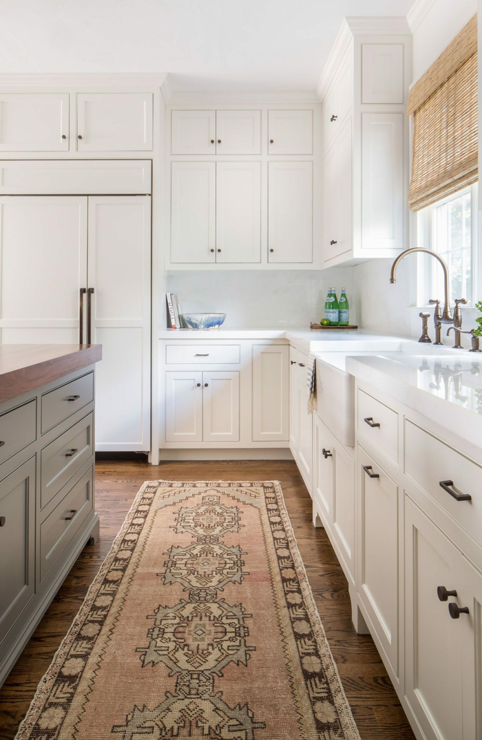 cuisine en longueur, tapis persan, meubles blancs, rideau en matériel naturel, îlot avec rangement en bois et blanc