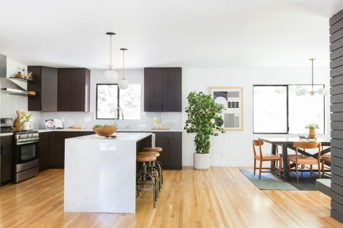 parquet clair dans la cuisine, îlot de cuisine blanc, tabourets en bois et métal, placards de cuisine bois foncé, grande plante verte