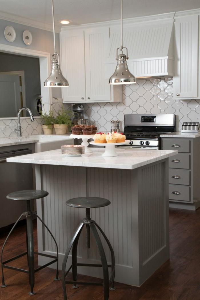 tabourets gris, petit îlot gris et blanc, lampes industrielles chromées, carrelage mural blanc, petite cuisine avec ilot