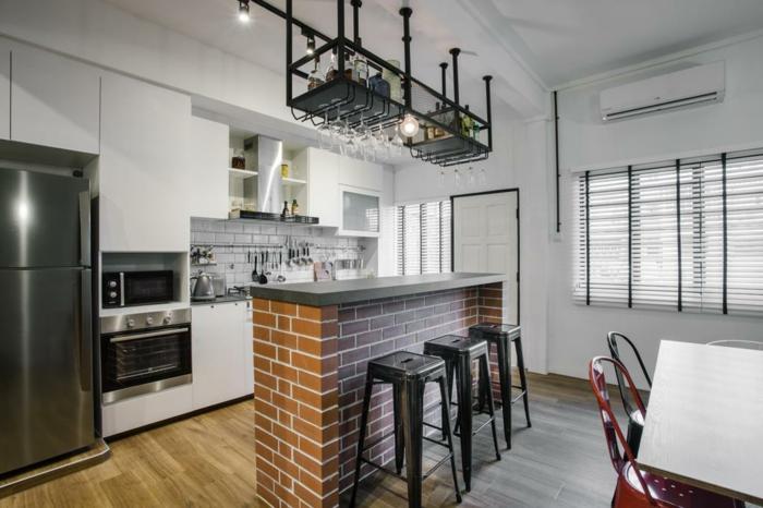 cuisine indutrielle, bar en briques rouges, tabourets noirs, éclairage industriel, verres suspendus, table de repas et chaises rouges