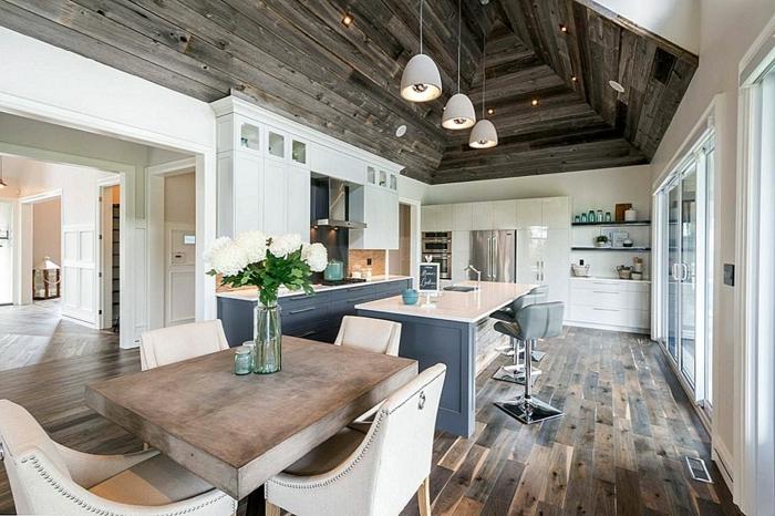grande cuisine rustique moderne, table de repas en bois, grandes chaises confortables, plafond en planches de bois, îlot avec évier et parquet cuisine aux nervures