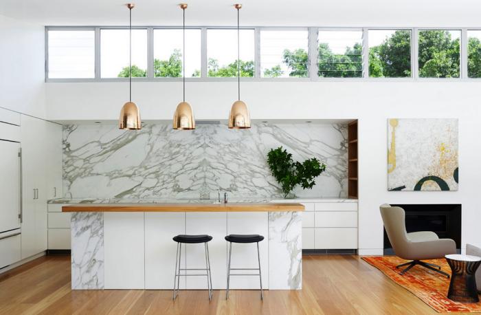 cuisine style svandinave, parquet en bois naturel, parquet vernis, trois lampes cuivrées, tapis orange