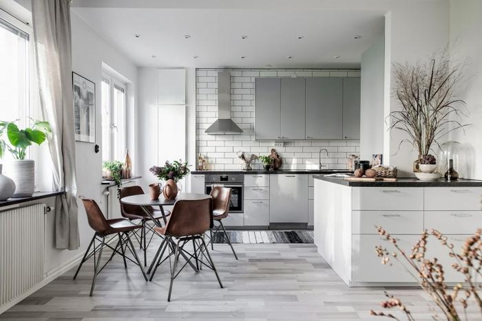 sol cuisine parquet gris, chaises design scandinave, plans de travail noirs avec placards blancs, carrelage métro, cuisine scandinave