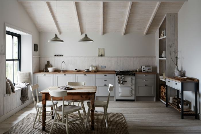 table en bois carrée, chaises rustiques, tapis en jute, plafond en pente, lampes suspendues, sol en bois, cuisine rustique industrielle