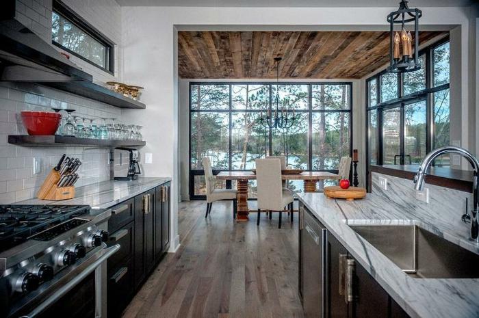 cuisine style chalet aux couleurs contrastantes, placards noirs, comptoirs marbrés, plafond en bois aspect rustique, îlot bois et marbre