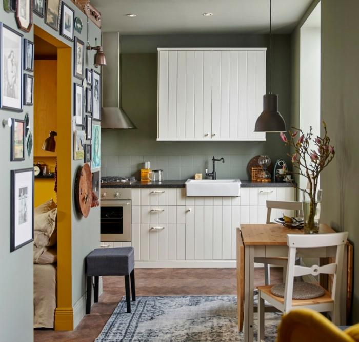 plan petite cuisine, gris et blanc, table rabattable bois et blanc, tapis gris, armoire suspendue blanche, photos en cadres