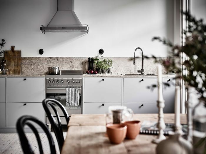 cuisine industrielle, placards gris, grande table en bois rustique, petits pots en argile