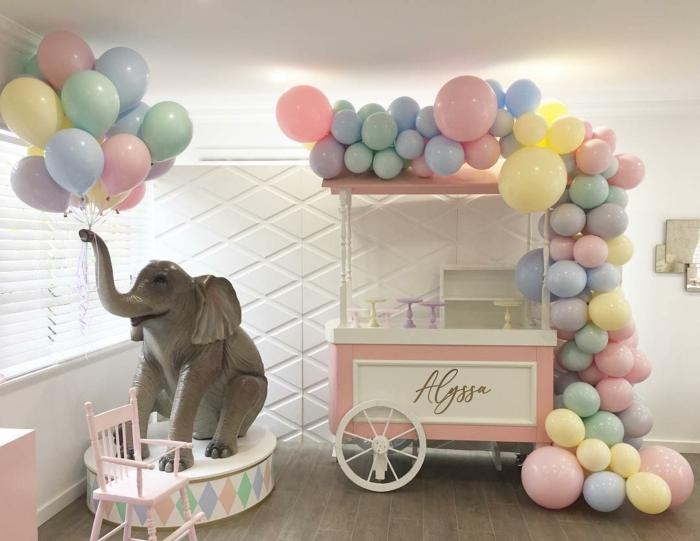 jouet éléphant qui porte une brassée de ballons, charrette en rose et blanc décorée d'une arche en ballons de tailles et couleurs diverses
