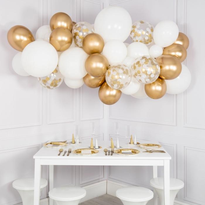 déco de fête nuage de ballons dorés et blancs, table blanche arrangée avec assiettes en blanc et doré, ballons à paillettes