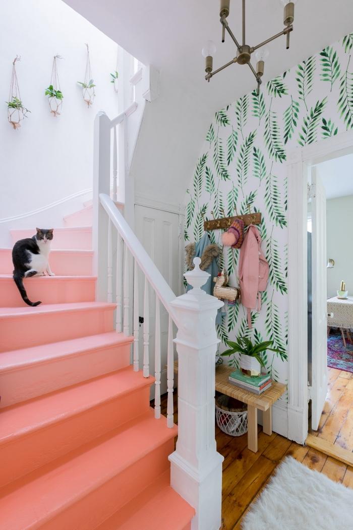 idée originale pour relooker un escalier en bois, déco cage d'escalier d'ambiance estivale et tropicale avec marches peintes en rose pastel et un papier peint à motifs végétaux