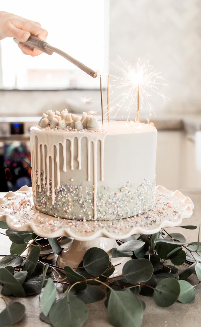 gateau pinata féerique au glaçage coulant de chocolat blanc décoré de perles en sucre nacrées, garni de poudre comestible, perles en sucre et guimauves