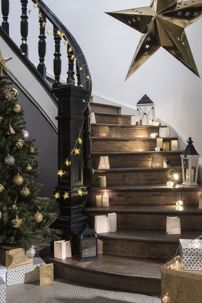 deco cage d'escalier féerique pour la fête de noël, de petites bougies et des lanternes qui illuminent l'escalier en bois et noir