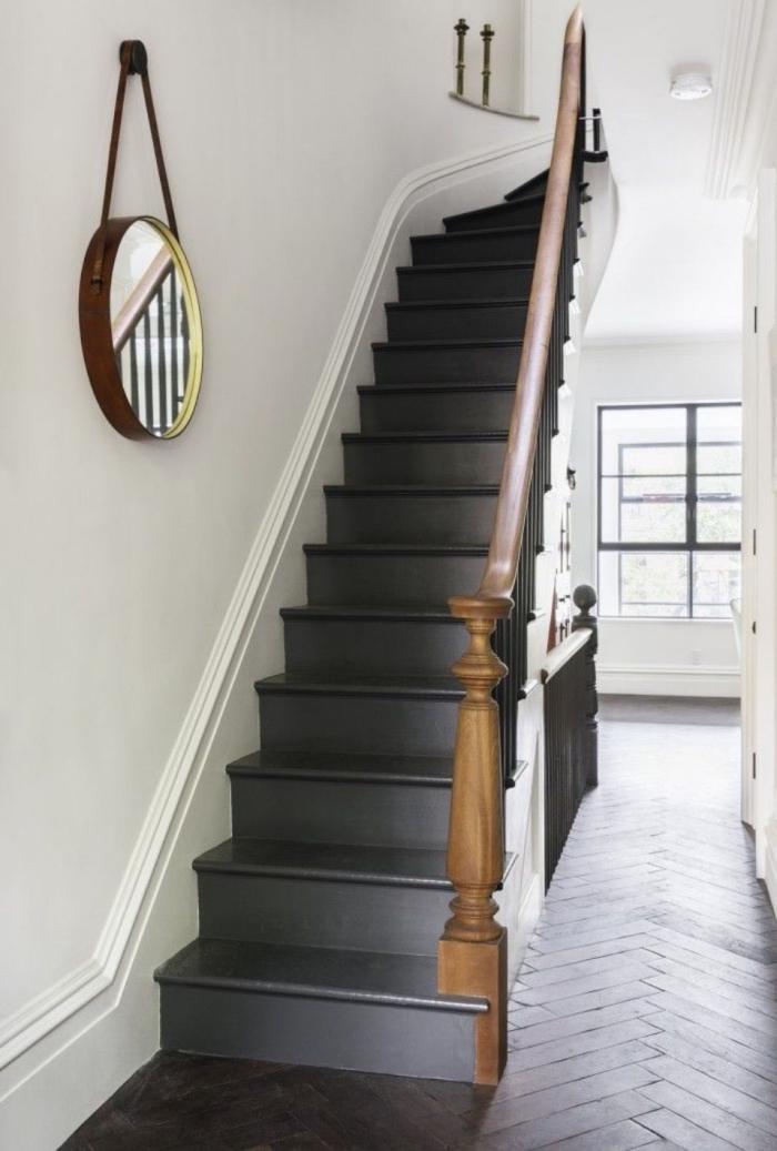 intérieur vintage scandinave avec un escalier noir et bois qui se détache sur le fond blanc des murs