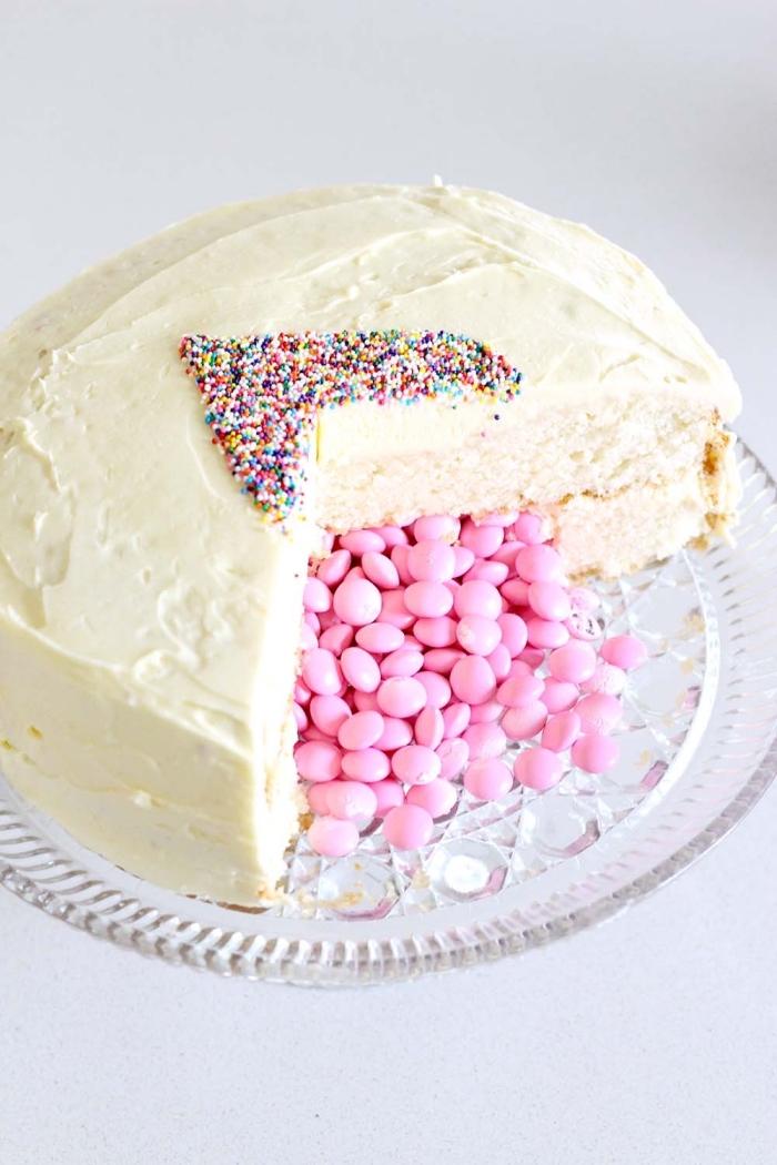 recette de gateau surprise spécial saint-valentin composé de deux couches de génoise à la vanille aérienne rempli de bonbons roses avec un simple décor de vermicelles au sucre en forme de coeur