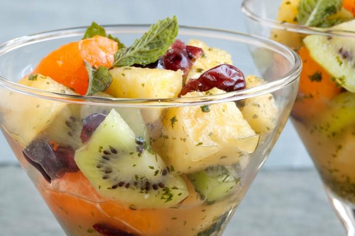 deux bols de verre pleins de fruits frais et séchés, ananas, kiwis, cerises séchées, feuilles de menthe, mandarines