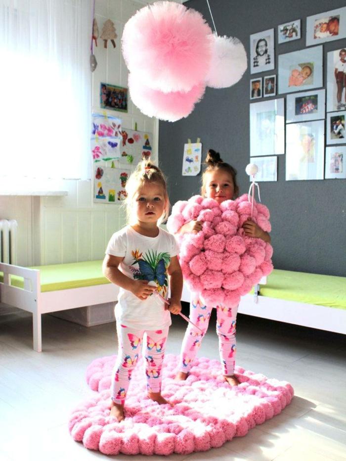 chambre d'enfant décorée de tapis et de coussin pompon en forme de coeur, suspensions rondes en tulle rose et deux petites filles