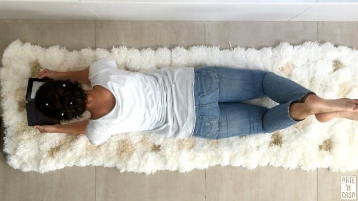jeune femme allongée sur son tapis blanc habillée en jeans bleus et t-shirt blanc, tapis pompons blancs