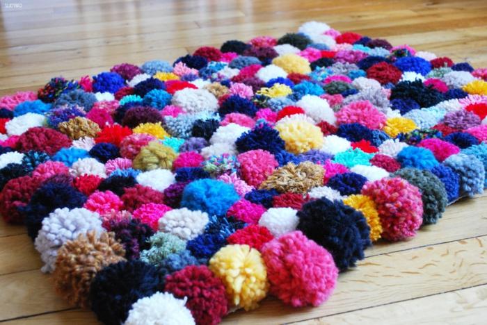 tapis en pompon, plusieurs pompons colorés en teintes vives, sol en bois, comment faire un tapis pompon