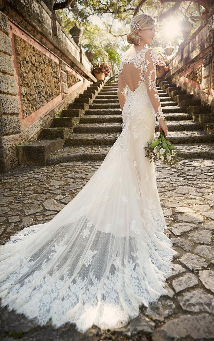 exemple de coiffure de mariée aux cheveux en chignon bas avec accessoire de tête en cristaux, robe de mariée 2018 à dos nu