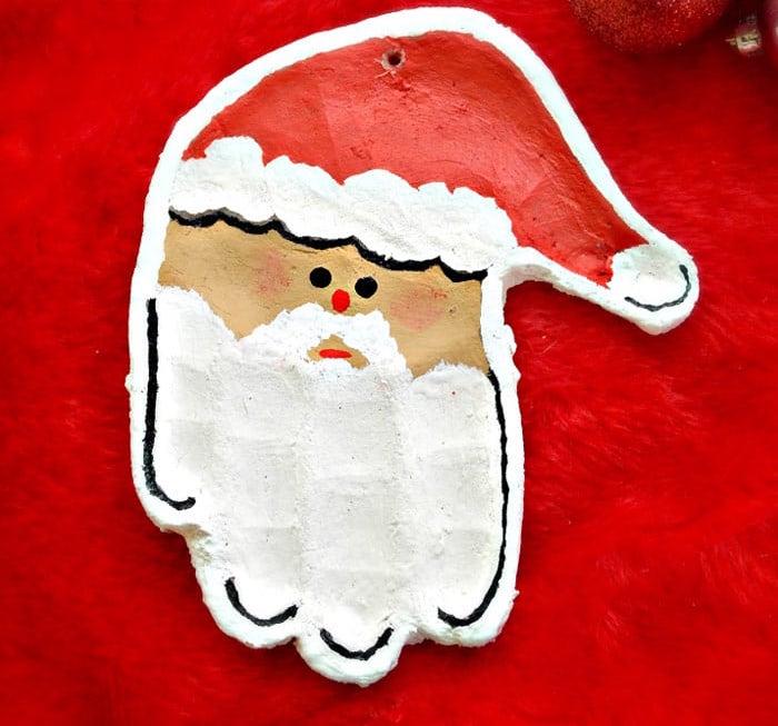 idée moulage en pate à sel en forme de tete de père noel avec empreintes de main et peinture blanc rouge