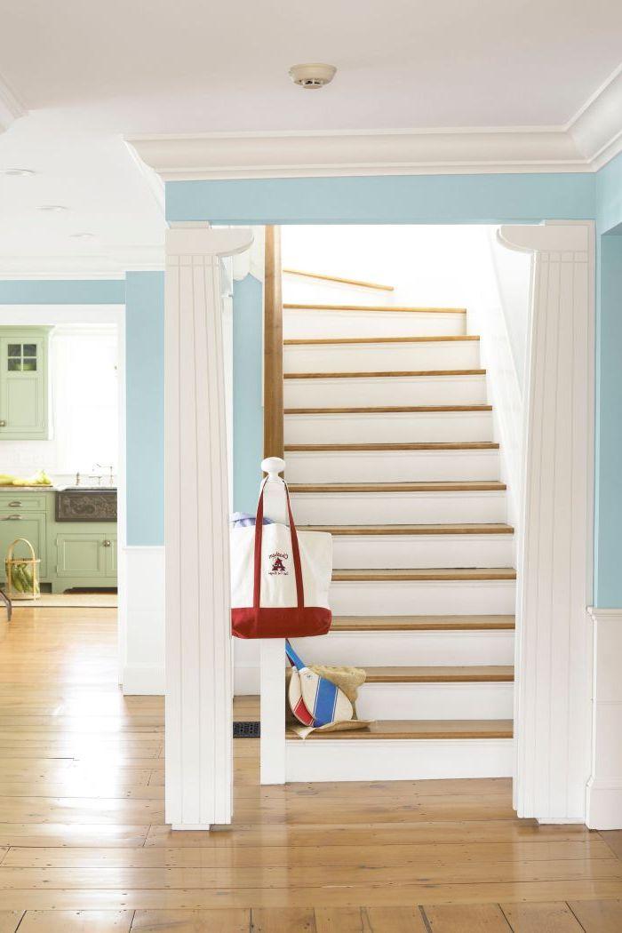 escalier bois et blanc plein de luminosité qui s'accorde parfaitement avec l'ambiance claire de l'entrée blanc et bleu ciel