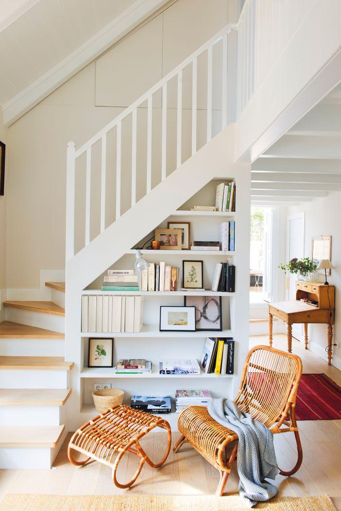 escalier bois et blanc au design épuré avec un rangement intégré pour une entrée esthétique et fonctionnelle, déco de salon tendance avec un fauteuil et repose-pied en rotin