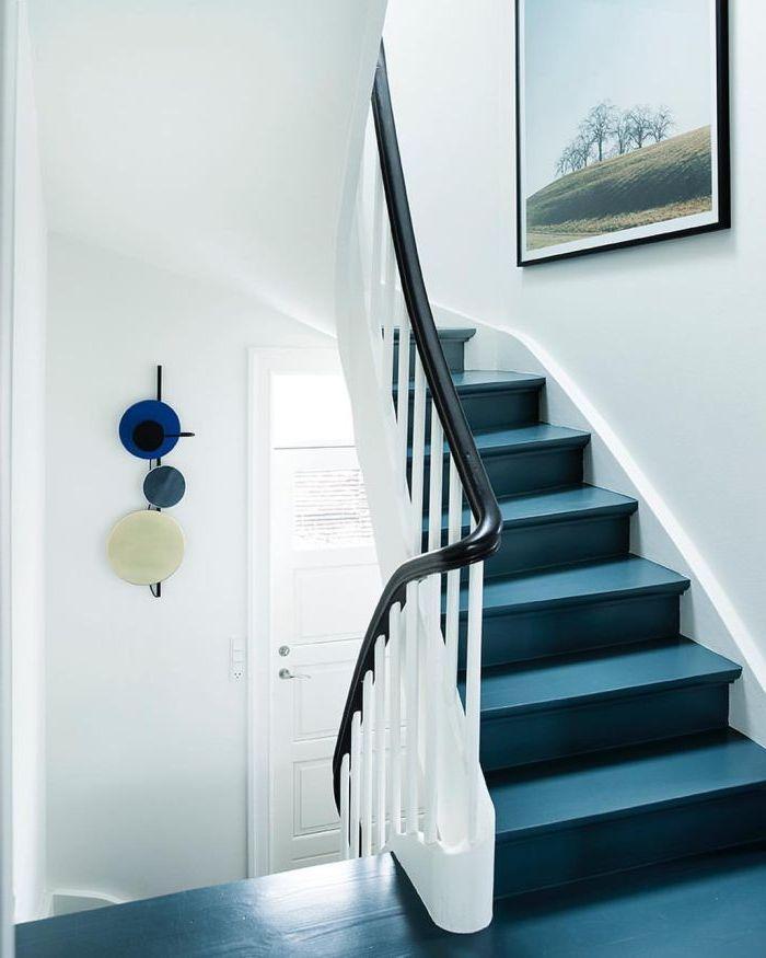 repeindre un escalier en bleu pétrole pour lui donner un look contemporain, des touches de noir sur le garde-corps et le cadre photo apportent de l'élégance à la cage d'escalier
