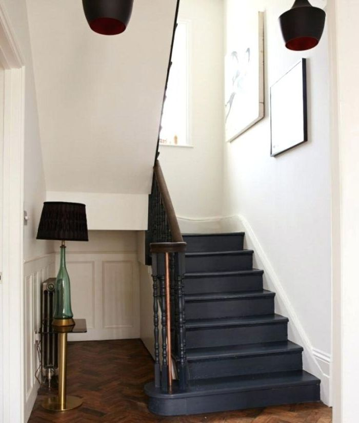 repeindre un escalier en bois tout en noir pour la mettre en valeur dans une cage d'escalier blanc de style scandinave