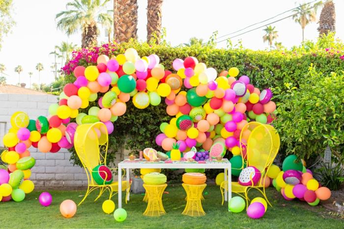 grande arche de ballons multicolores, chaises et tabourets jaunes, pelouse verte, haie verte