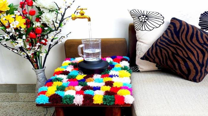 table de chevet décorée d'un tapis pompon multicolore, bouquet de fleurs artificielles, coussins décoratifs motifs animaux