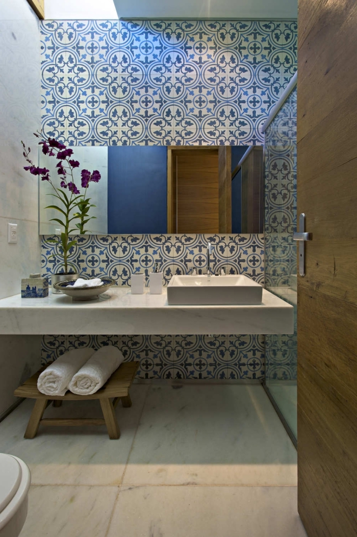 les carreaux de ciment à larges motifs bleus habille le mur derrière la vasque et jouent le rôle d'une haute crédence originale