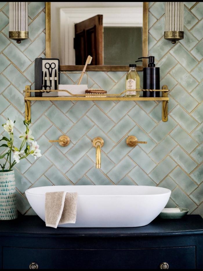 crédence élégante en mise en valeur par le robinet mural et l'étagère dorée, posée en dessus d'un meuble sous vasque bleu marine