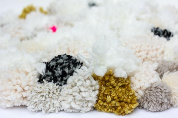 tapis de pompons fantastique en couleurs claires, pompons blancs épais, accents en gris et jaune