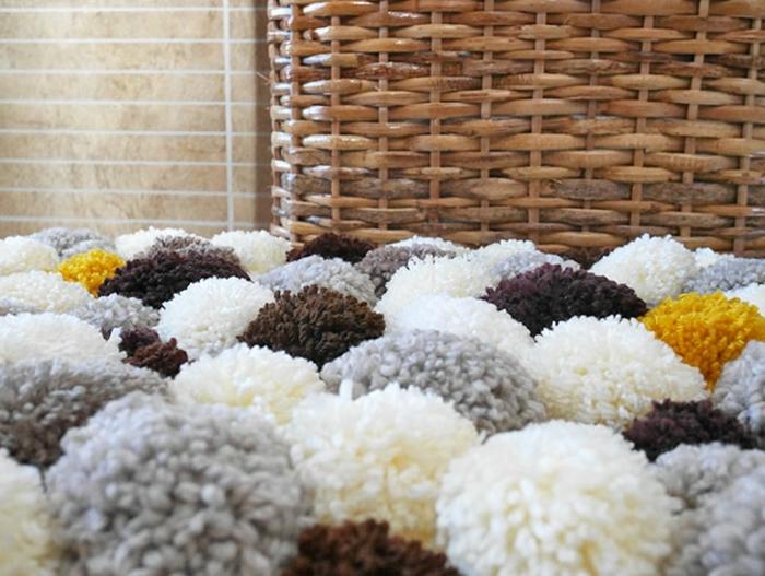 grand panier rustique en fibres tressés et tapis pompons, pompons gris blancs, jaunes, marron assemblés en joli tapis