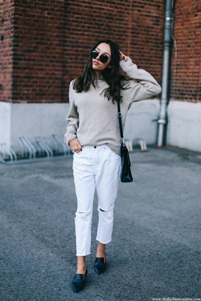 pantalon blanc, pull gris, lunettes de soleil, cheveux noirs, sac noir, mur en briques rouges