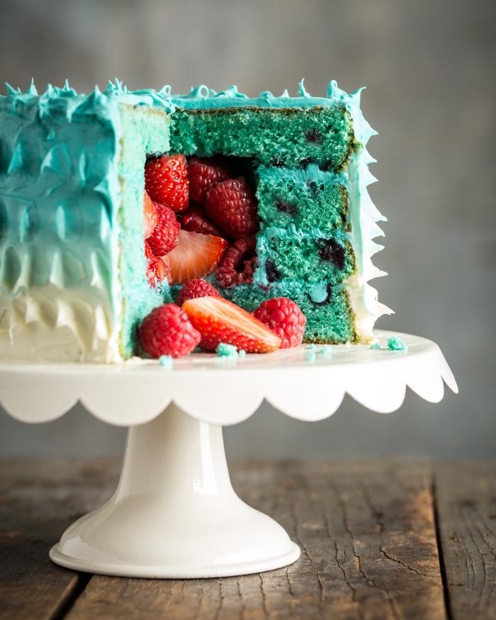 recette de gateau pinata au glaçage dégradé en version healthy rempli de fruits frais déposé sur un présentoir à gâteaux blanc