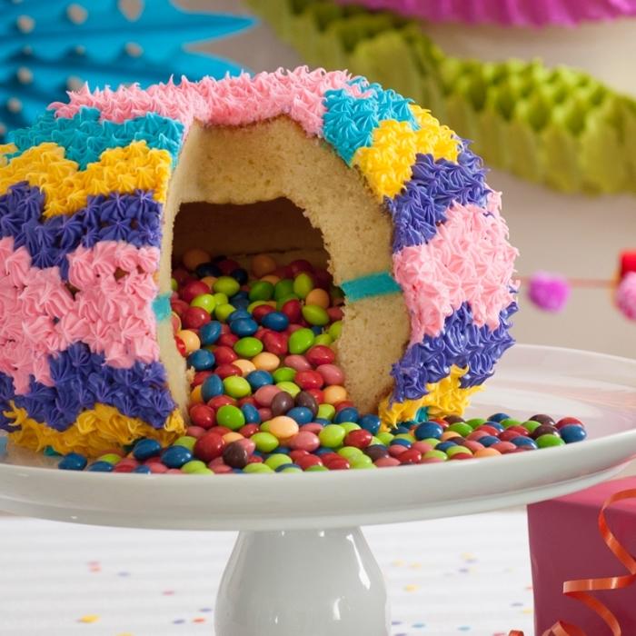 pinata cake en forme de sphère avec un centre creux rempli de bonbons, au glaçage coloré réalisé à la poche à douille décorative
