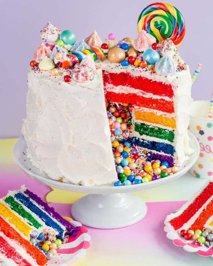 gateau arc en ciel composé de génoises de couleurs différentes fourré de petits bonbons, nappé de crème pâtissière nature et décoré avec des meringues