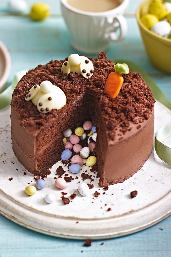 pinata cake au chocolat décoré pour pâques avec deux lapins en pâte d'amande avec têtes plongées dans le gâteau
