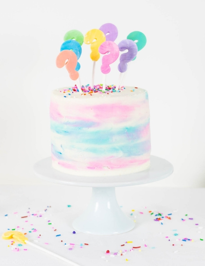 délicieux pinata cake pour un baby shower, gâteau au glaçage aquarelle rempli de bonbons roses, décoré de cake toppers points d'exclamation