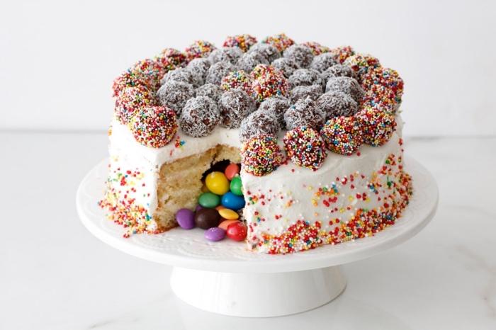 gateau vanille moelleux fourré de smarties au glaçage de beurre, décoré avec des boules chocolat et coco