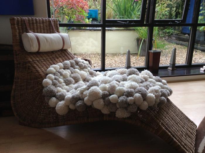 grand fauteuil en fibres de rotin, tapis en blanc et gris fait avec une multitude de pompons, intérieur de maison moderne
