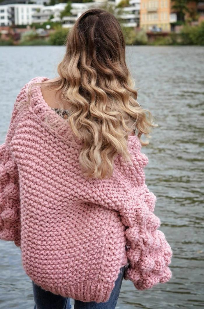 pull oversize femme rose, manches originales, gros pull en maille porté par une femme blonde au bord de la rivière