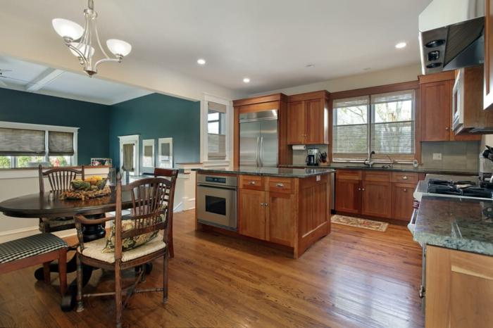 parquet de cuisine laqué, table en bois ovale, murs bleus, îlot en bois avec électroménager