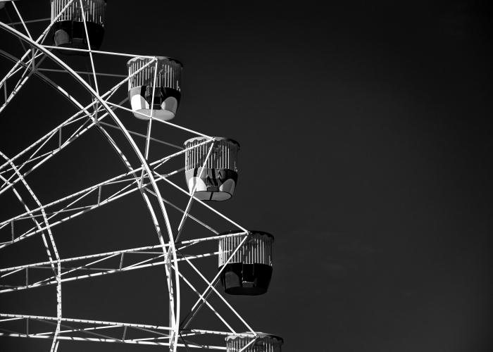 belle photo noir et blanc artistique d'une roue géante qui se détache sur le fond du ciel noir, photographie monochrome