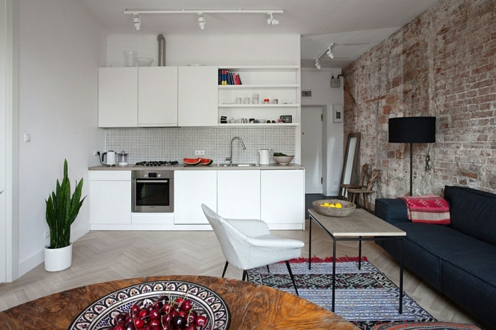 cuisine studio, grande table ronde, tapis rayé, mur en briques, lampe de sol noire, armoires suspendues